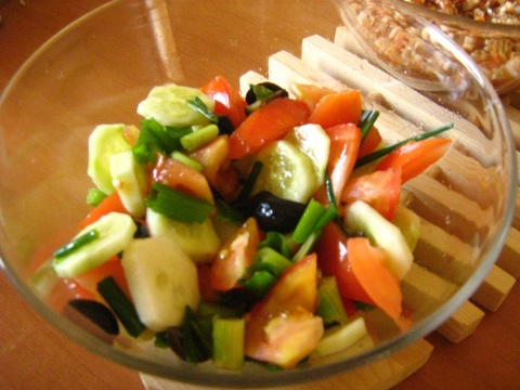 Fresh salad from tomatoes, cucumber, onion, olives and a squeeze of a lemon